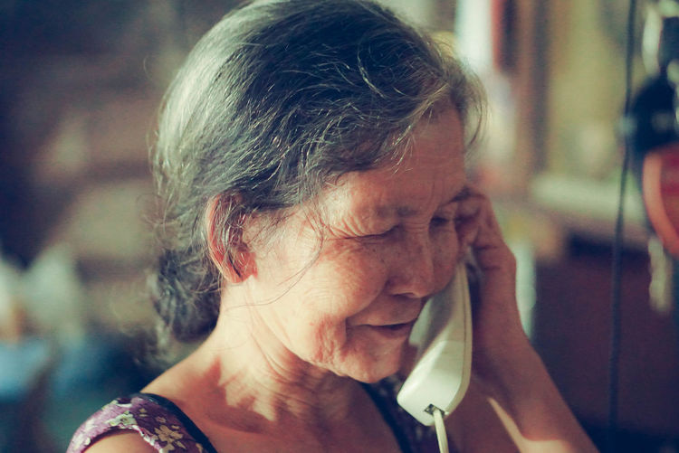 Close-up of senior woman talking on telephone at home