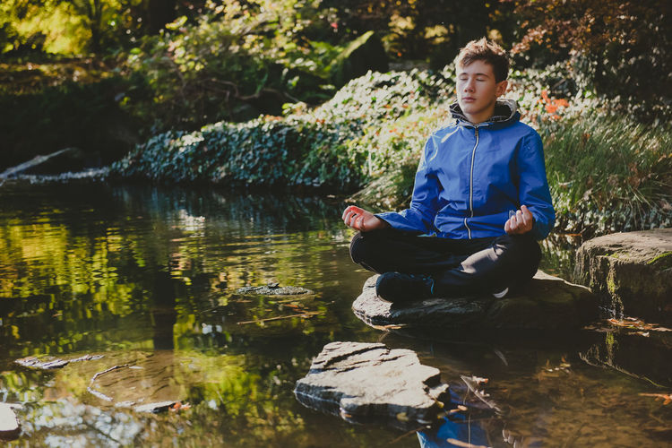 Teenage boy meditating and relaxing in a city park japanese garden. outdoor meditation