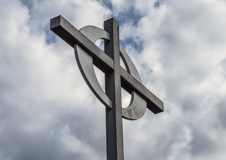 Low angle view of cross on street light against sky