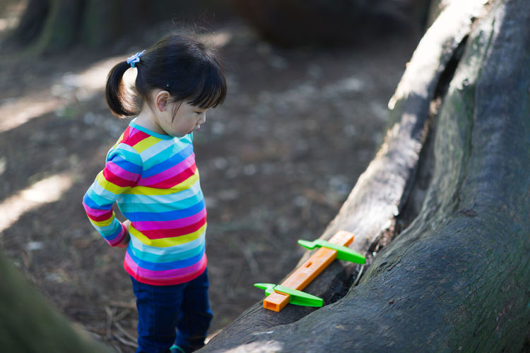 Young girl playing outdoor measure-mate in the forest park for leaning measurement