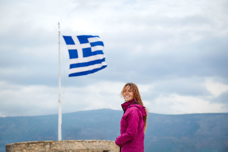 Young happy woman standing in front of the Greek flag at the Acropolis. Athens, Greece. Antique Athens, Greece Autumn Cloudy European  Freedom Greek Happy Hope Parthenon Peace Student Tourist View Woman Youth Athens Awesome Backgrounds Blue Sky Caucasian Girl Greece person Traveler