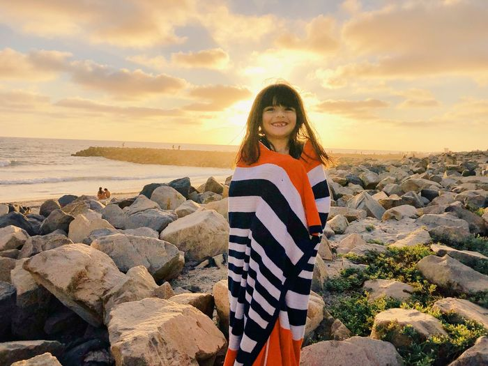 Smiling girl wrapped in towel while standing on rocks at beach against sky during sunset