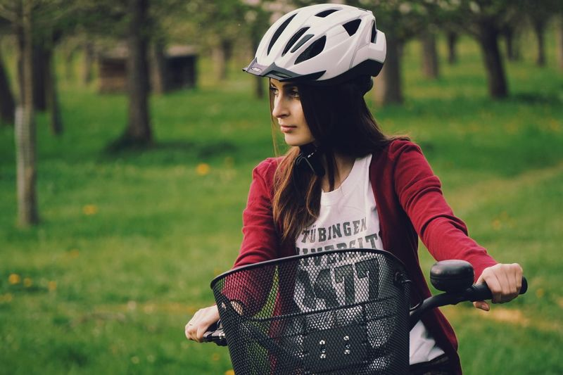 Young woman with bicycle standing on grass