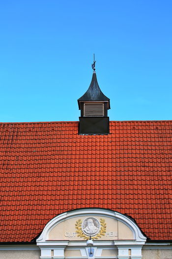 Low angle view of cross on roof of building against clear sky