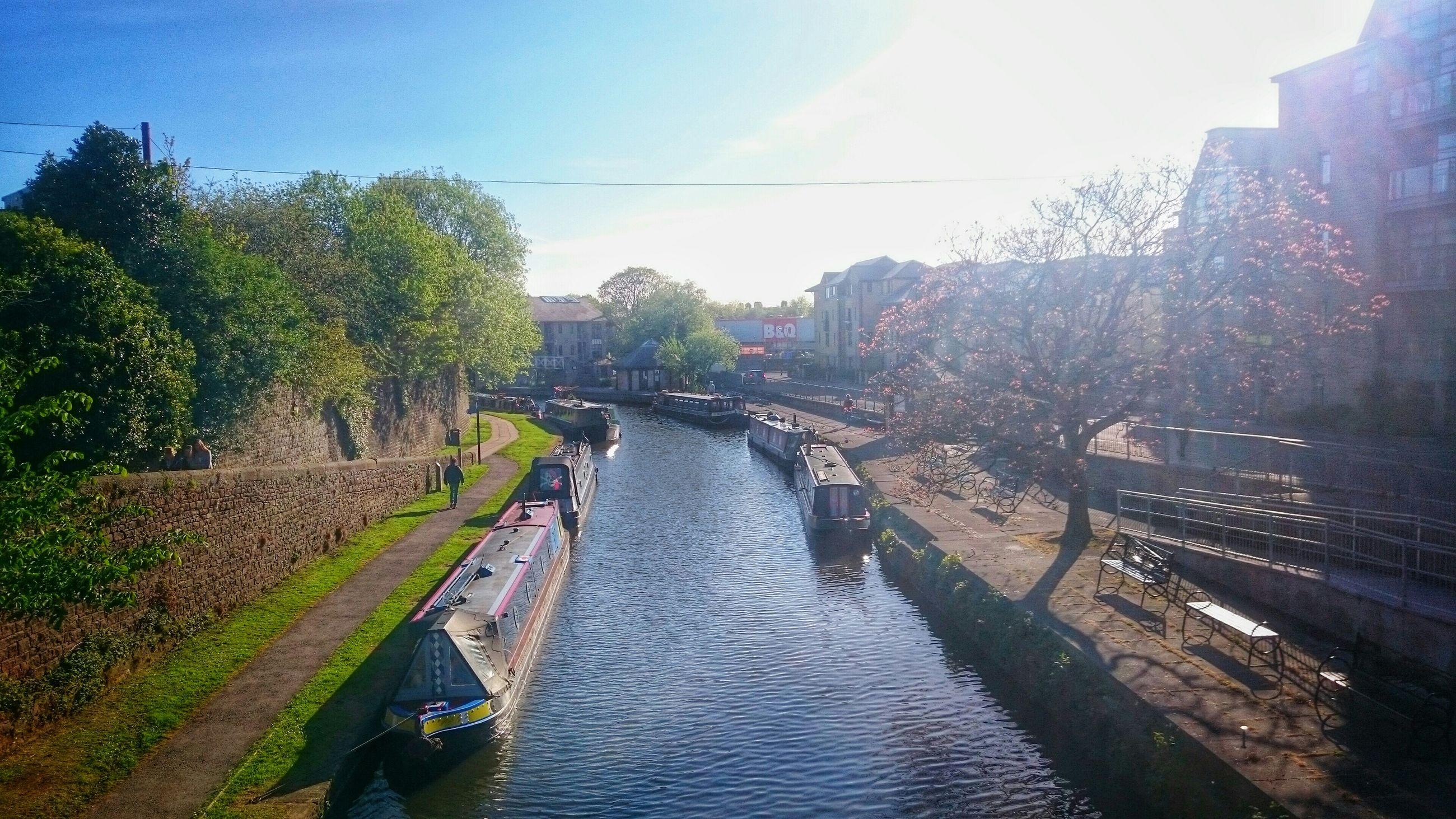 built structure, architecture, water, canal, building exterior, tree, bridge - man made structure, connection, river, transportation, the way forward, sky, diminishing perspective, sunlight, men, waterfront, lifestyles, vanishing point, incidental people