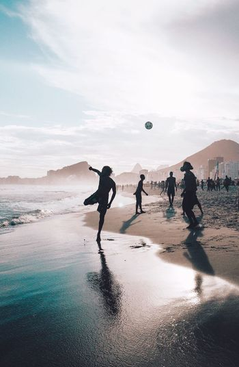 People playing soccer on beach against sky