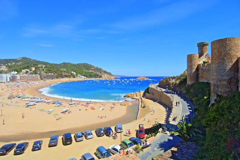 High angle view of cars parked at beach against clear blue sky in tossa de mar