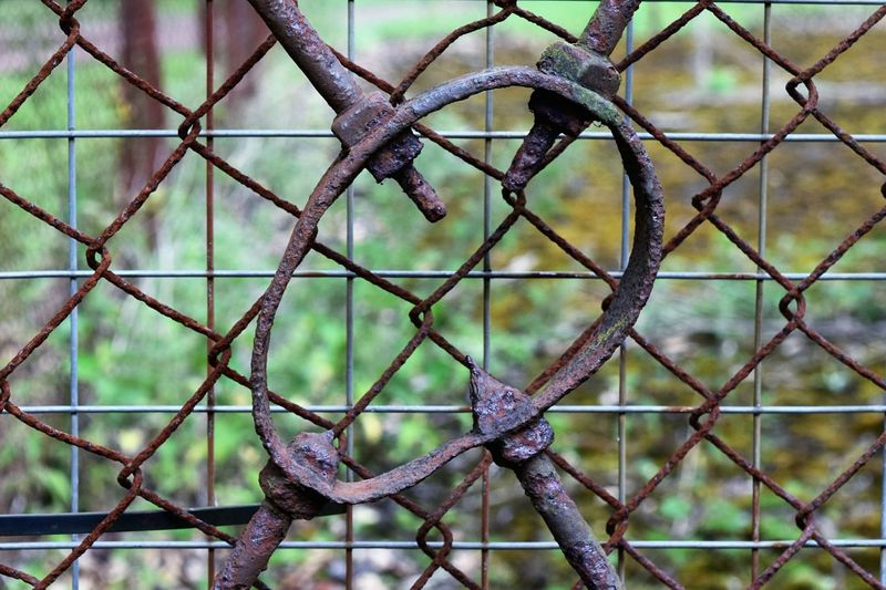 Old rusty metal against chainlink fence