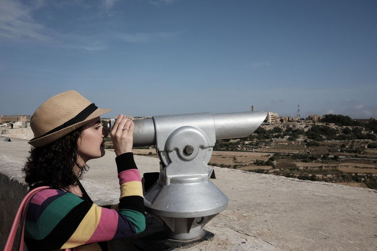 Woman Looking Through Coin-Operated Binoculars Against Sky