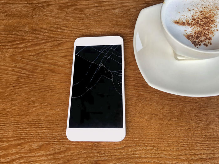 Mobile cracked tuchscreens for communications is brocken placed on a wooden table and coffee mugs in coffee shop Coffee Coffee Cup Table Mug Coffee - Drink Wireless Technology Drink Cup Technology Communication Food And Drink Refreshment Saucer Connection Wood - Material Indoors  Portable Information Device Still Life Smart Phone High Angle View No People Crockery