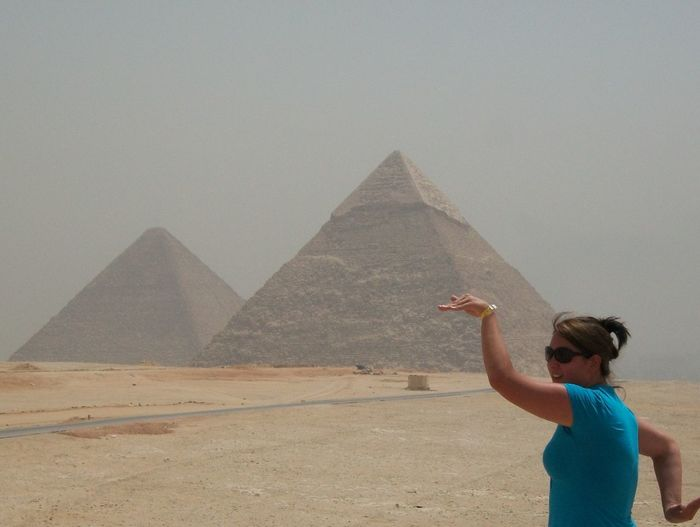 Young woman enjoying at great pyramid of giza against sky