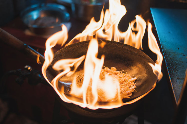 Burning Fire Heat - Temperature Flame Fire - Natural Phenomenon Food And Drink Close-up Food No People Indoors  Motion Kitchen Utensil High Angle View Freshness Long Exposure Nature Preparation  Glowing Appliance Focus On Foreground Street Food Noodles Vegetarian Food Chinatown Pan Wok