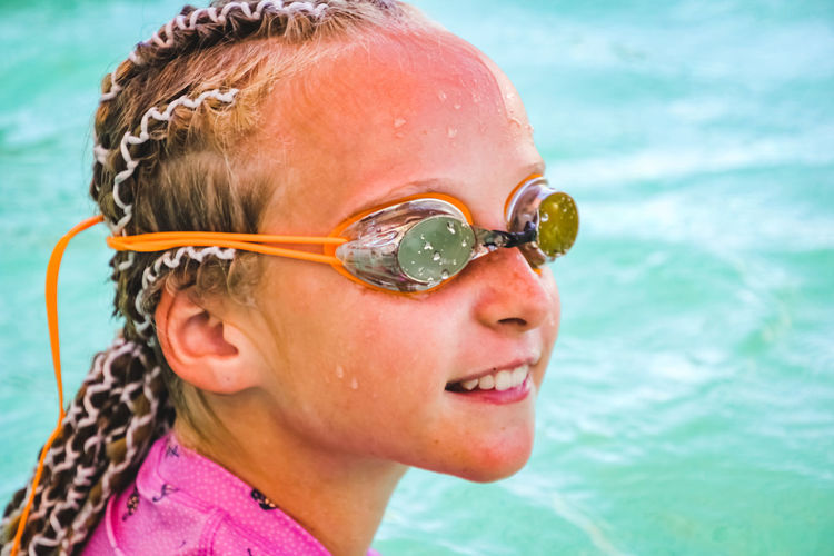 portrait of a young girl wearing swimming goggles poolside in summertime Headshot Child Childhood Water Portrait One Person Close-up Leisure Activity Girls Swimming Pool Real People Lifestyles Women Females Focus On Foreground Day Pool Swimwear Hairstyle Eyewear Outdoors Innocence Swimming Goggles