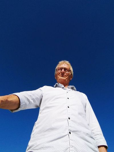 Low angle view of smiling senior man standing against clear blue sky