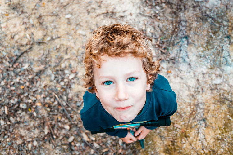 High angle view of boy standing outdoors