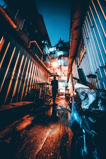 Rear view of man walking on illuminated city at night