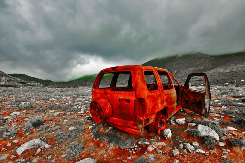 Burned Car Burned Earth Car Wreck Cloud - Sky Destroyed Destroyed Car Mountain No People Outdoors Red Storm Cloud Weather