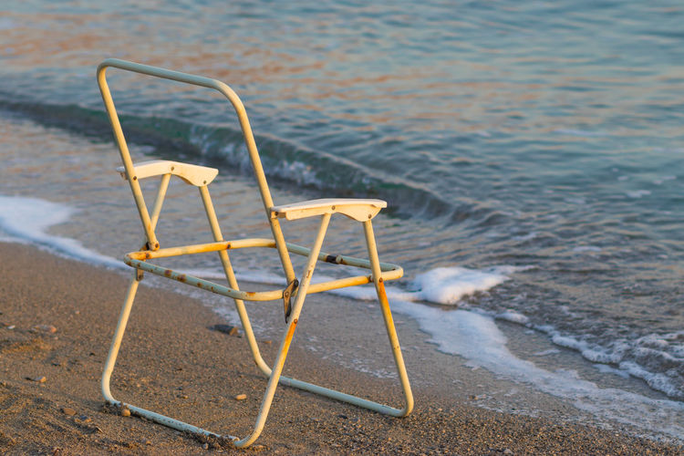 High angle view of empty chair on beach