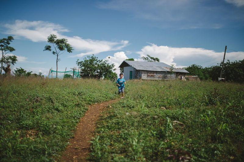Man walking on field against sky
