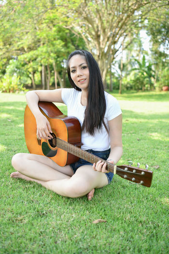 Portrait of young woman playing guitar while sitting against trees at park