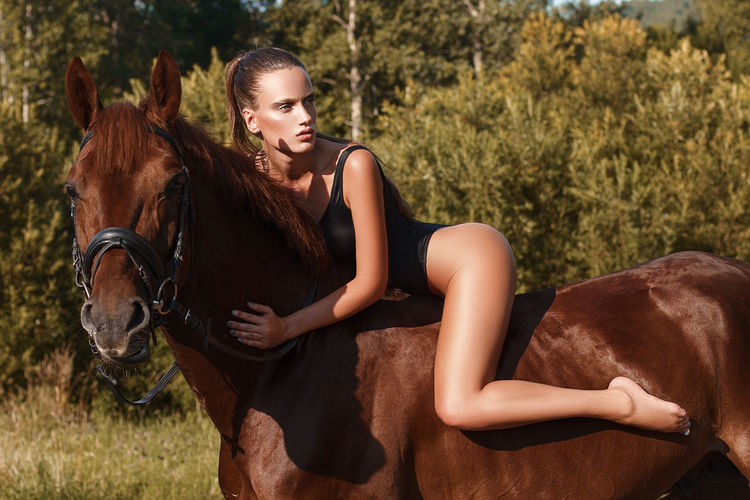 Seductive Woman Riding Brown Horse On Field