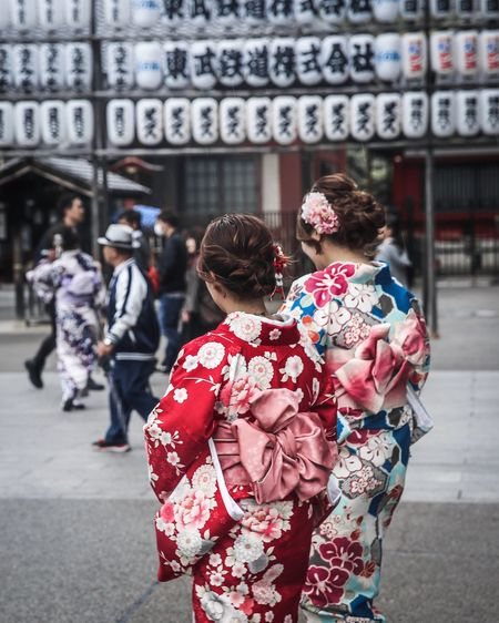 Rear View Of Woman In Kimonos Walking On Street