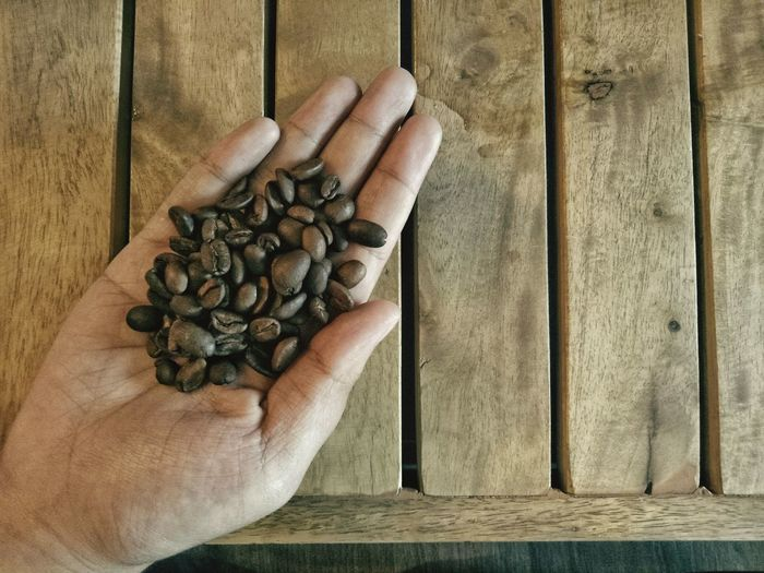Close-up of human hand holding roasted coffee beans over table