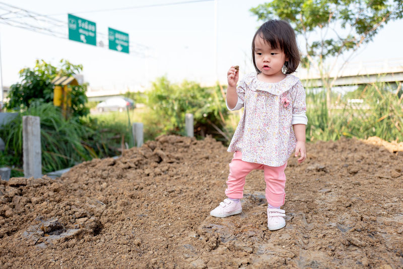 Child Childhood Full Length One Person Front View Innocence Plant Cute Nature Standing Casual Clothing Day Real People Girls Baby Portrait Shoe Outdoors Rubber Boot Hairstyle