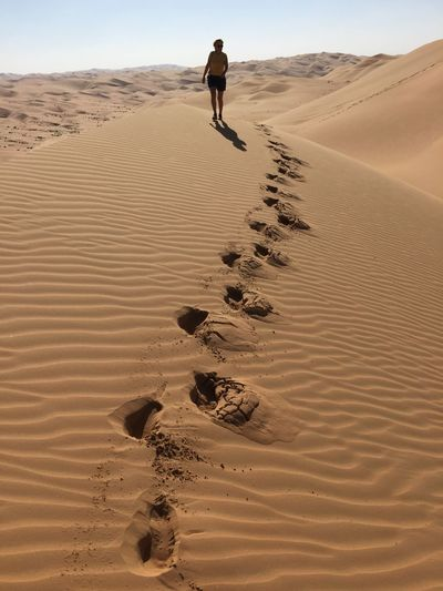 Woman walking on sand dune at desert