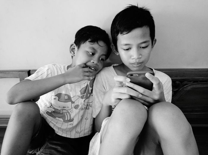 Friends sitting on mobile phone at home