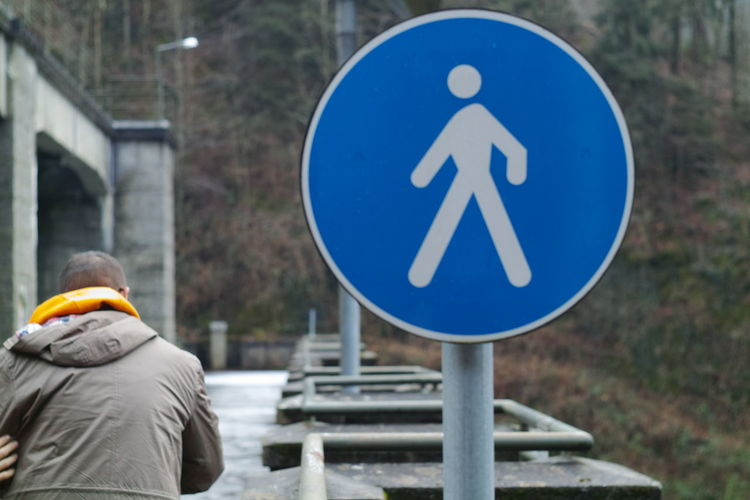 Rear view of man sign on road