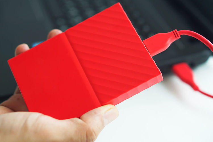 Close-up of hand holding red paper