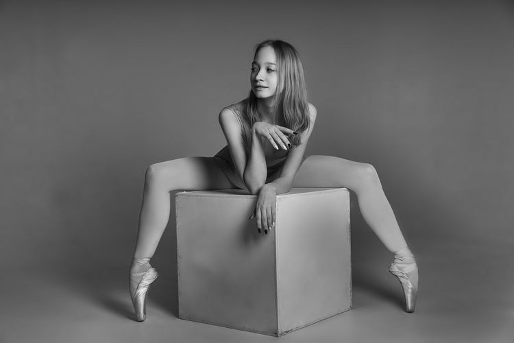 Young ballet dancer sitting on cube shape over gray background