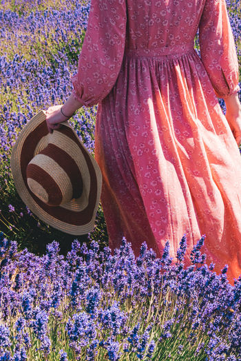 Close-up of woman holding purple flowering plants