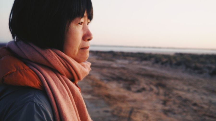 Side view of thoughtful mature woman looking away at beach against sky