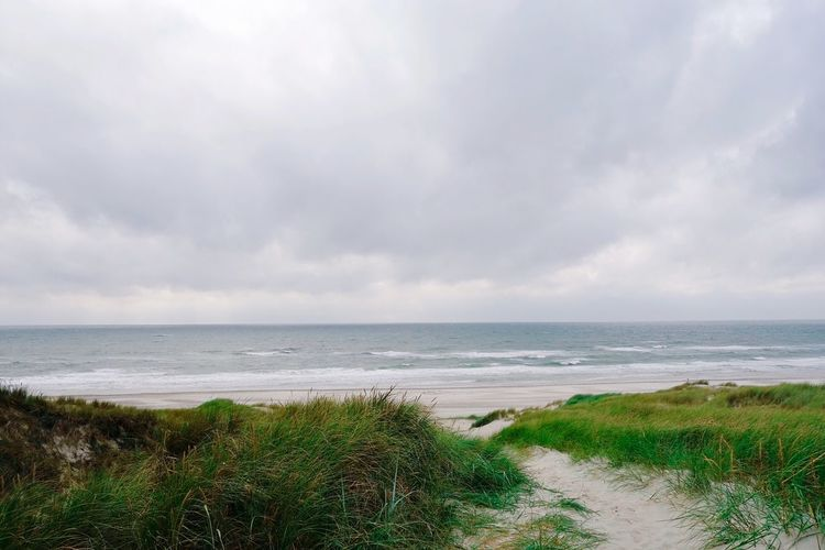 Scenic View Of Beach Against Cloudy Sky