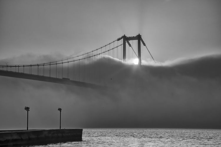 View of suspension bridge against cloudy sky and fog