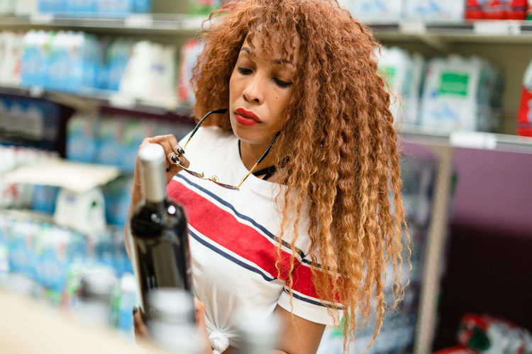 Close-Up Of Woman Looking At Wine Bottle While Standing At Store