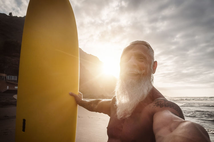 Portrait of shirtless man in sea against sky