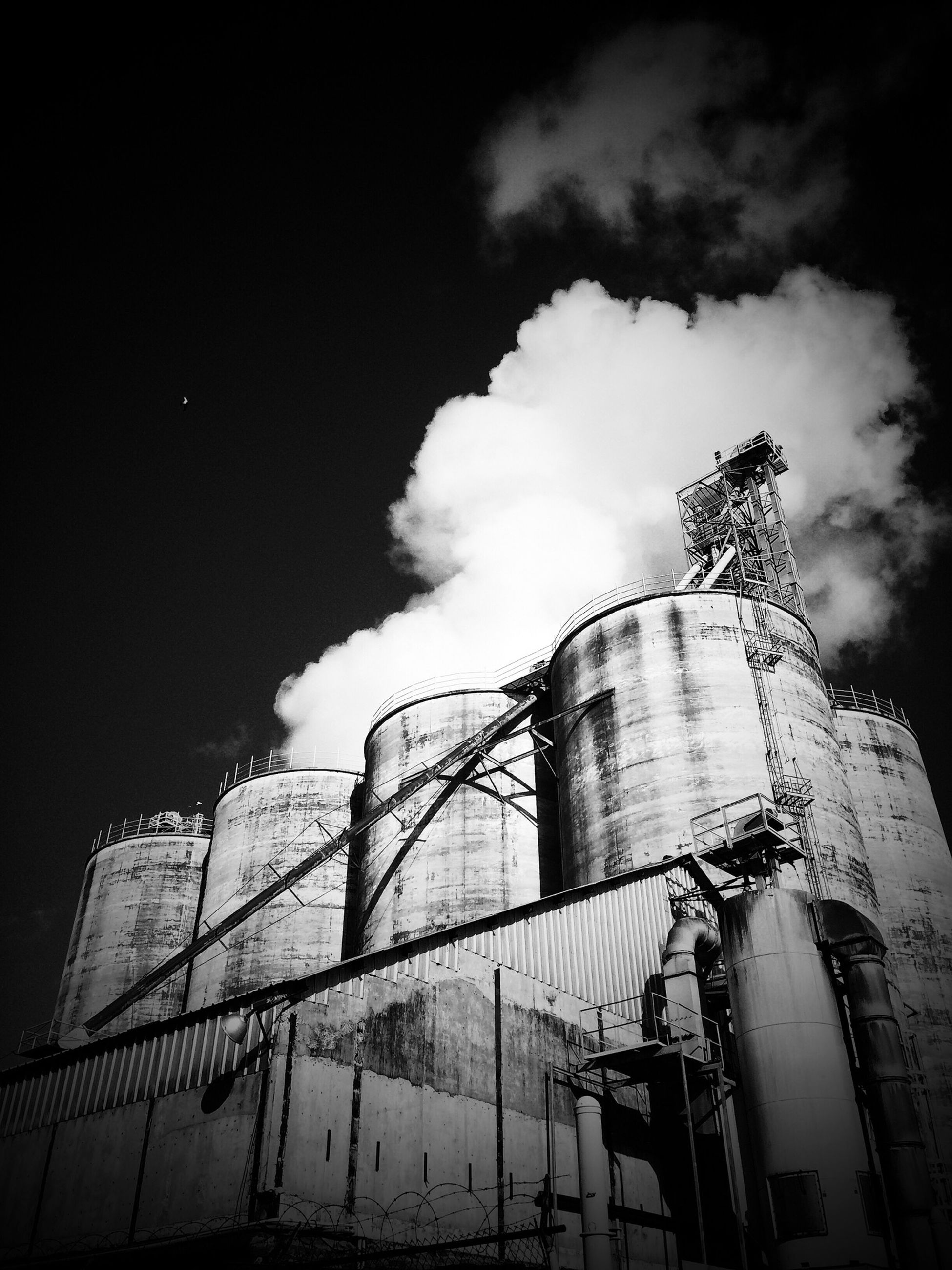 architecture, built structure, building exterior, low angle view, sky, cloud - sky, cloudy, building, construction site, cloud, tower, factory, outdoors, industry, tall - high, development, day, no people, weather, metal