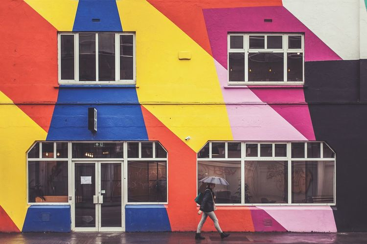 Low section of person on multi colored residential building