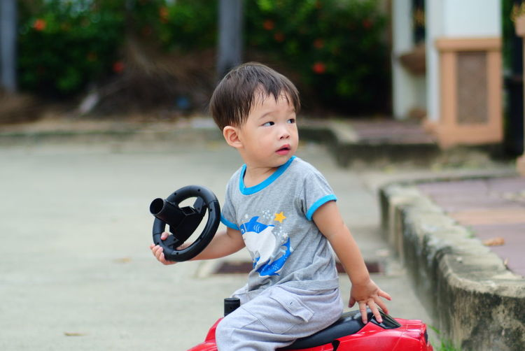 Portrait of boy riding toy car