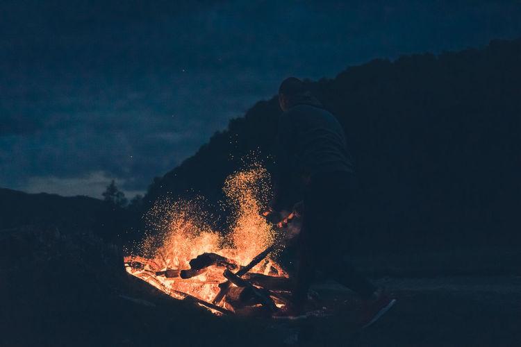 Man burning bonfire at night