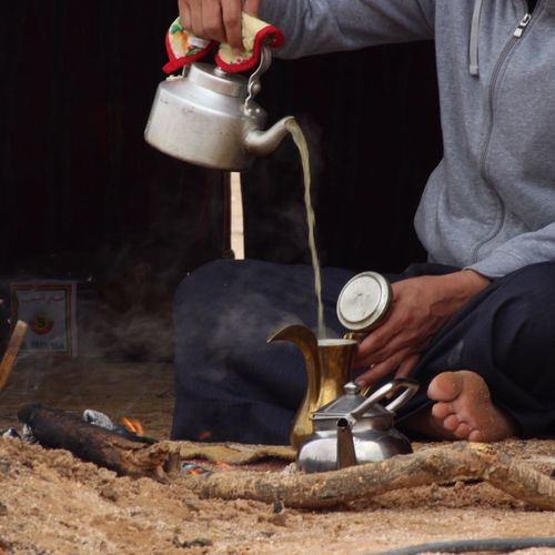 Midsection of man pouring tea