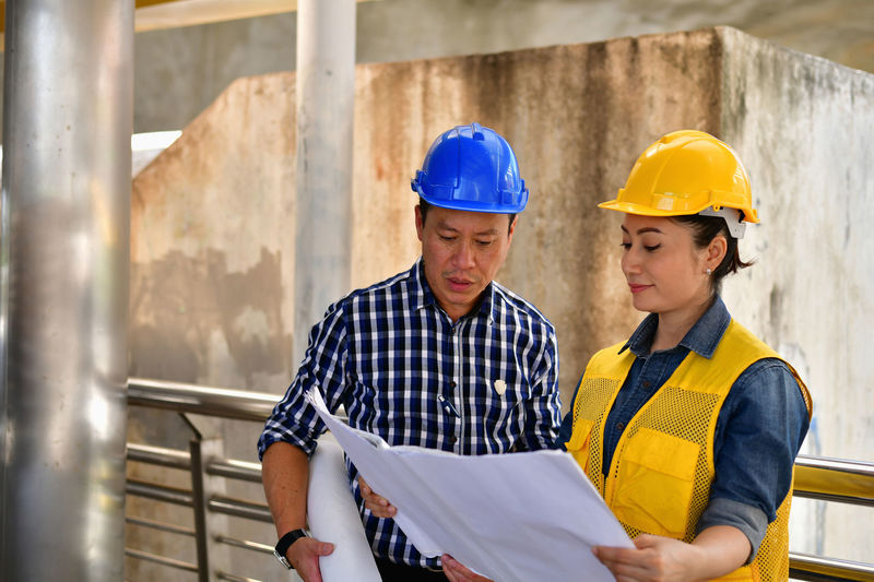 Concepts Business Engineering, Professional engineers, Young Business people are planning construction. Adult Analyzing ARCHITECT Architecture Asian  Background Blueprint Build Builder Business Businessman Businesspeople City Communication Construct Construction Cooperation Create Creator  Design Designer  Engineer Engineering Explaining  Female Hand Handshake Happiness Happy Helmet Industry Instrument Male Man Meeting Plan Planner Present Presentation Professional Project Shake Smiling Success Successful Talking Team Teamwork Woman Work