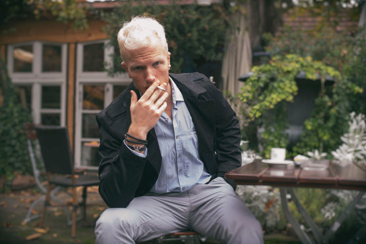Portrait of man smoking cigarette sitting by table at cafe