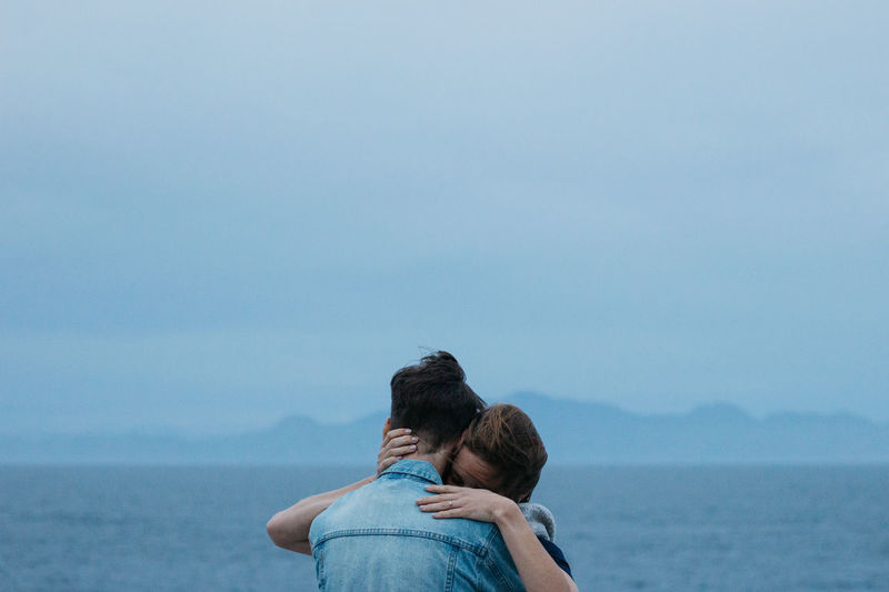 Rear view of couple on sea against sky