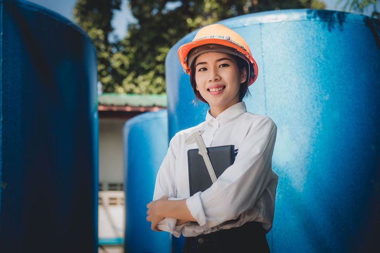 Portrait of smiling engineer standing by storage tanks at factory