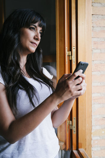 Young woman using mobile phone while standing by window at home
