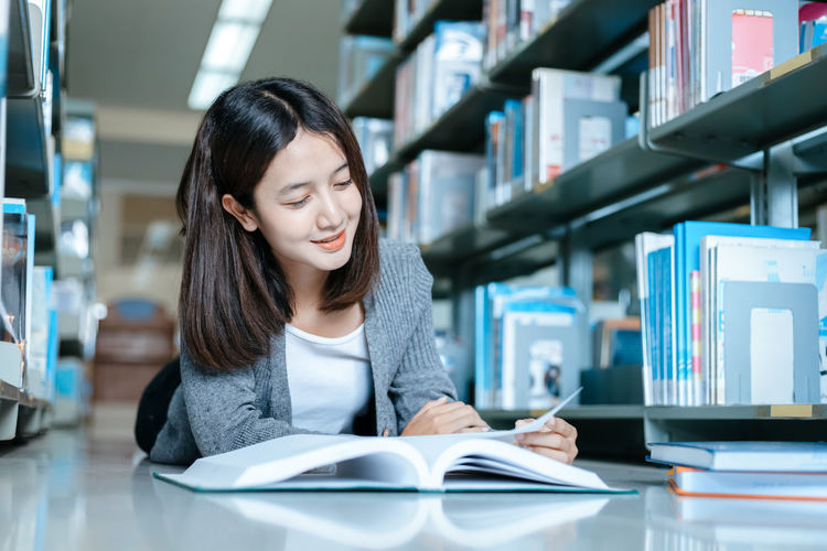 Smiling woman reading book lying on floor in library